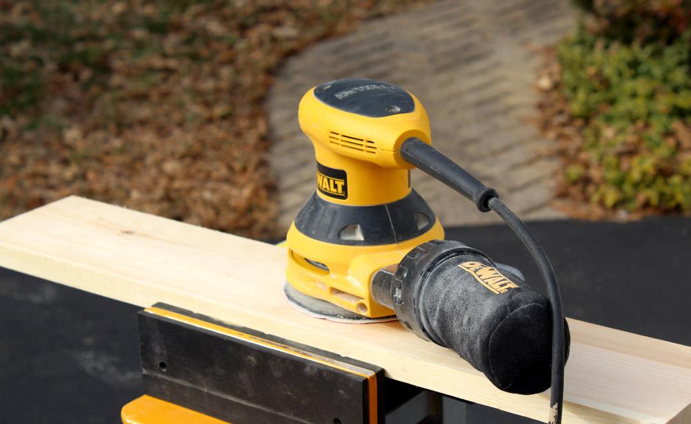 Sanding down scrap wood to make a DIY hook rack