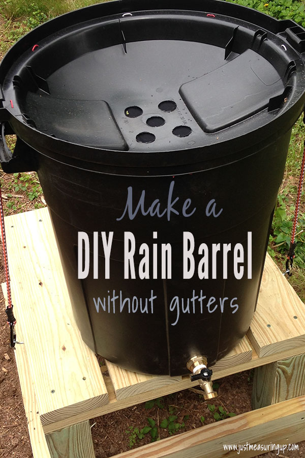 20 gallon trasn can on a wooden stand serving as a gutterless rain barrel system