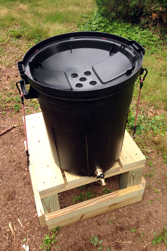DIY rainbarrel on a homemade stand in the garden, without using gutters