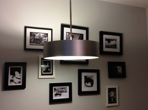 Wall gallery with black and white pictures and modern lighting