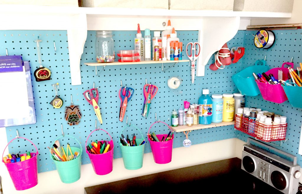 Blue pegboard mounted on the wall for easy craft room organization