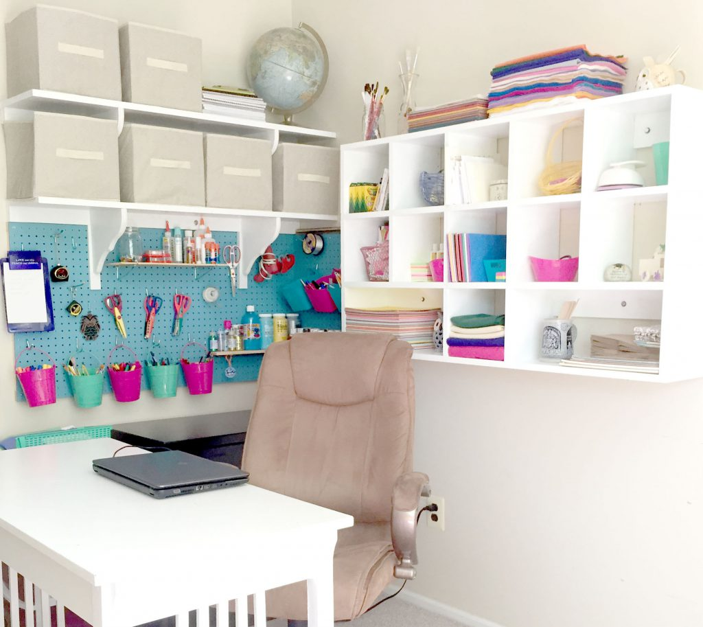 Craft corner organized with wall-mounted giant pegboard, cubby shelves, and diy wall shelves