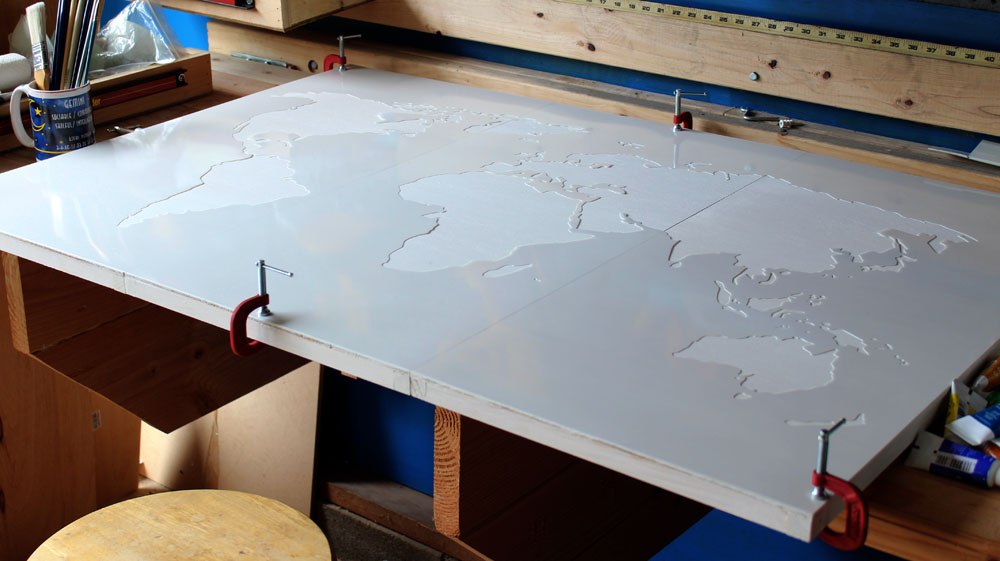Using a world map stencil to create DIY wall art