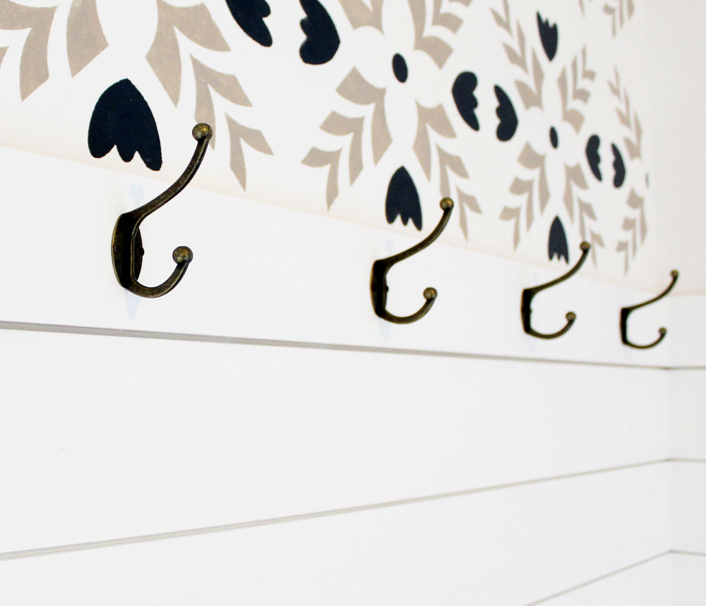 Shiplap accent wall with hooks and a beautiful stenciled wall