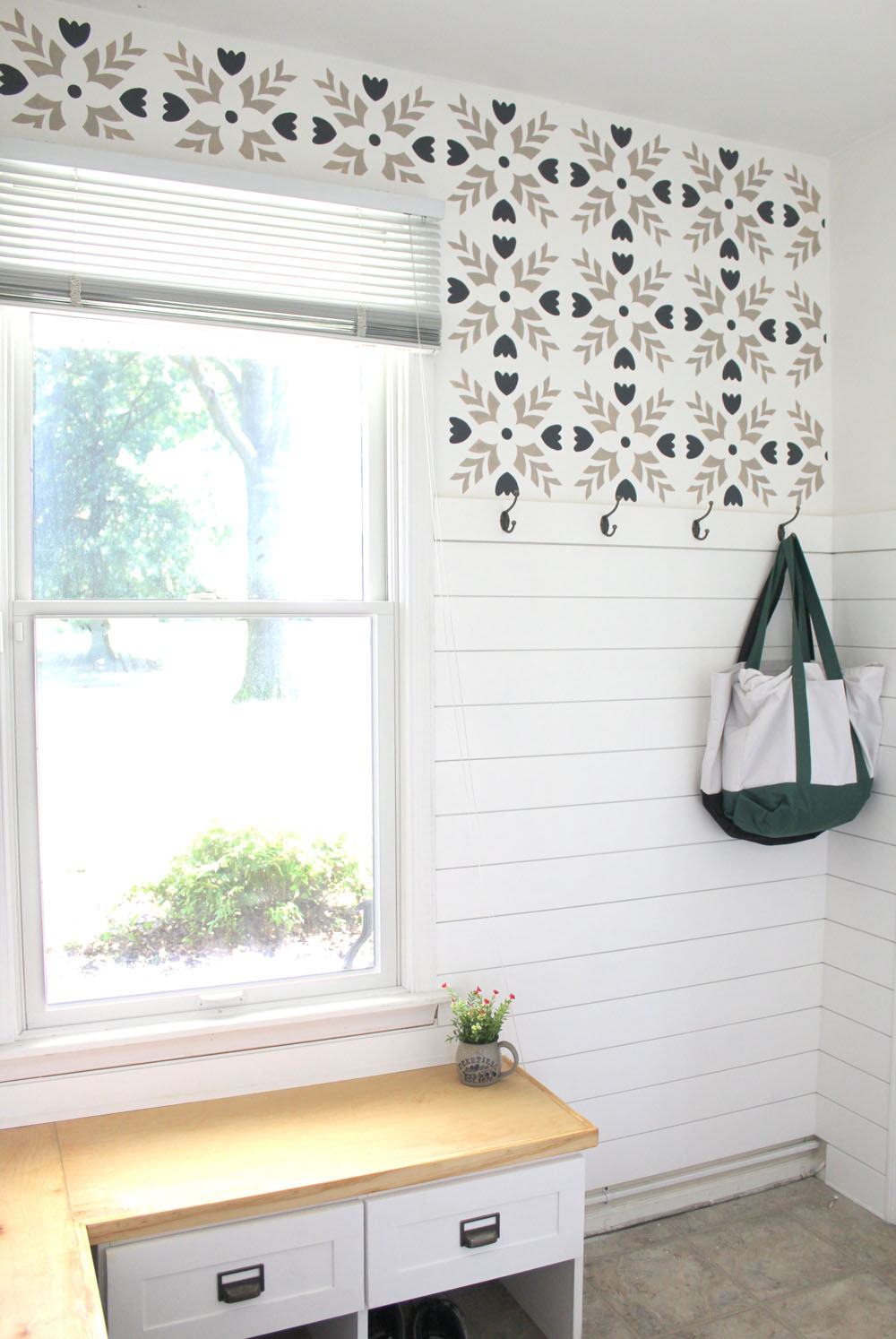 Stencil and shiplap mudroom wall with hooks and an L-shaped bench