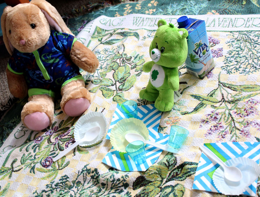 Stuffed animal picnic on floor with blanket