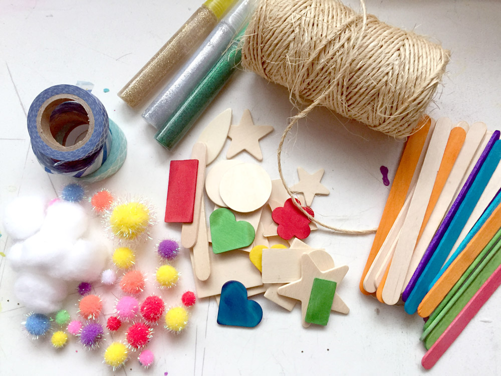 Materials used to make popsicle stick Christmas ornaments - pom poms, popsicle sticks, glitter, twine, washi tape, and wooden shapes