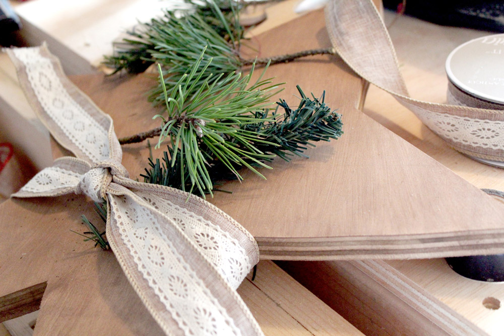 Arranging greenery onto a wooden Christmas tree star