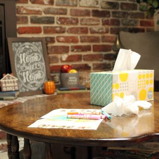 Tissue box and coloring sheets on coffee table