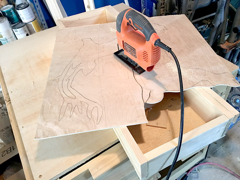 Cutting a reindeer yard decoration out of plywood with a jigsaw