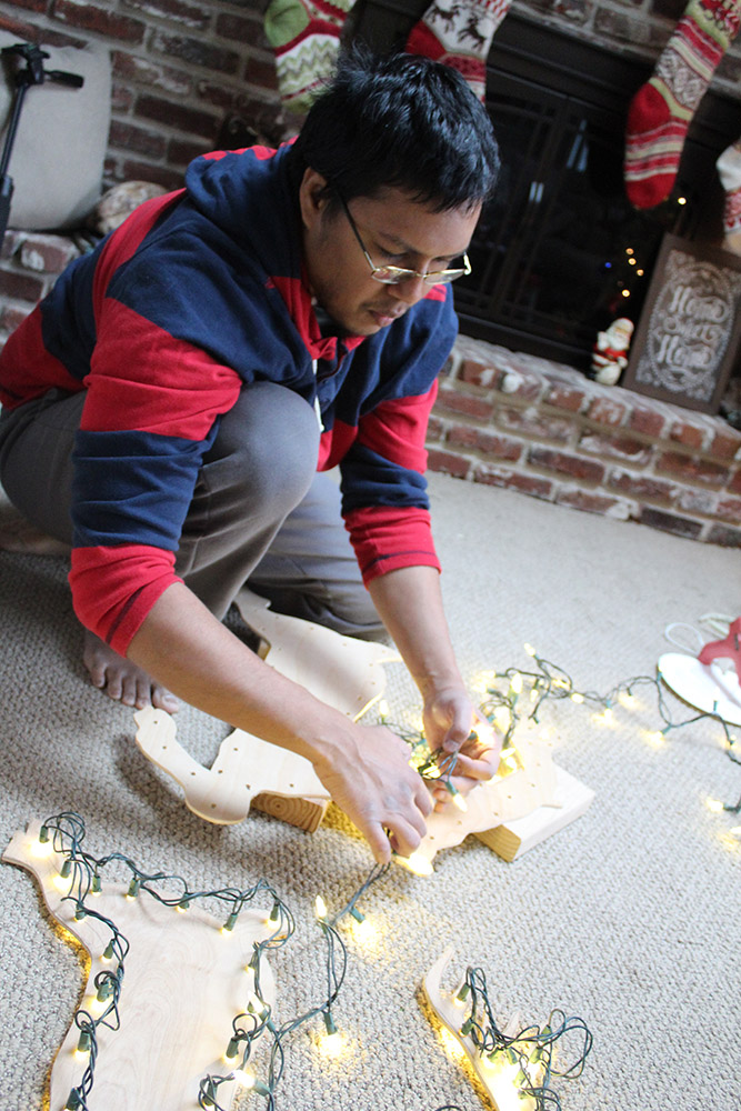 Poking the holiday lights through the drill holes on the plywood yard decorations