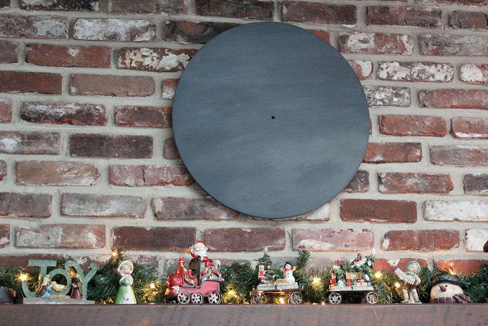 Chalkboard colored wall clock hanging above fireplace