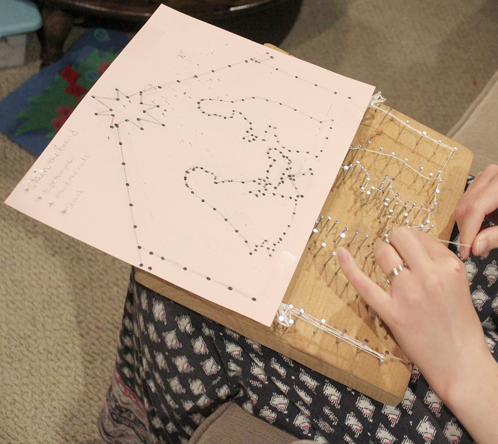 Wrapping string around nails in a wooden board to create DIY string art nativity scene