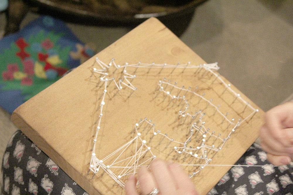 Wrapping string around nails to create nativity scene string art project