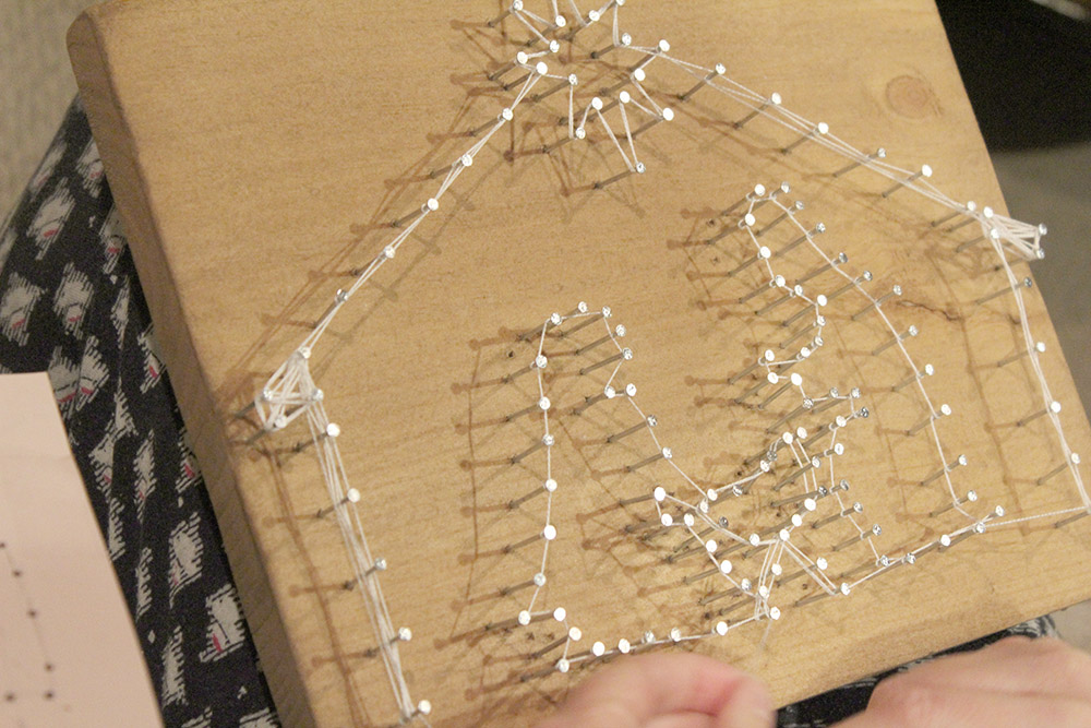 Making an outline with string for the DIY string art project nativity scene.