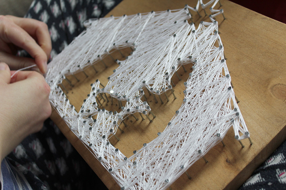 Using string and nails to create a beautiful string art nativity scene