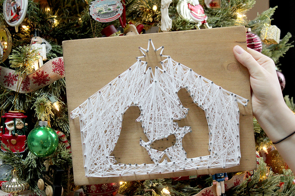 DIY nativity scene string art on wood held in front of colorful Christmas tree