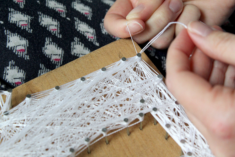 Tying the ends of the DIY string art as the final touch