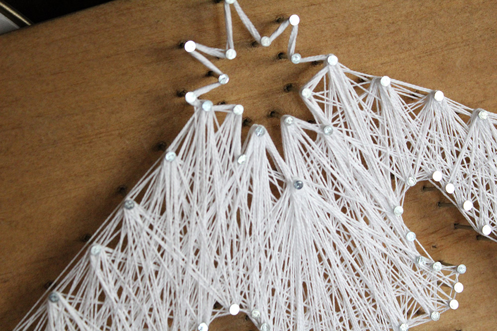 String art nativity star in white on a wooden board