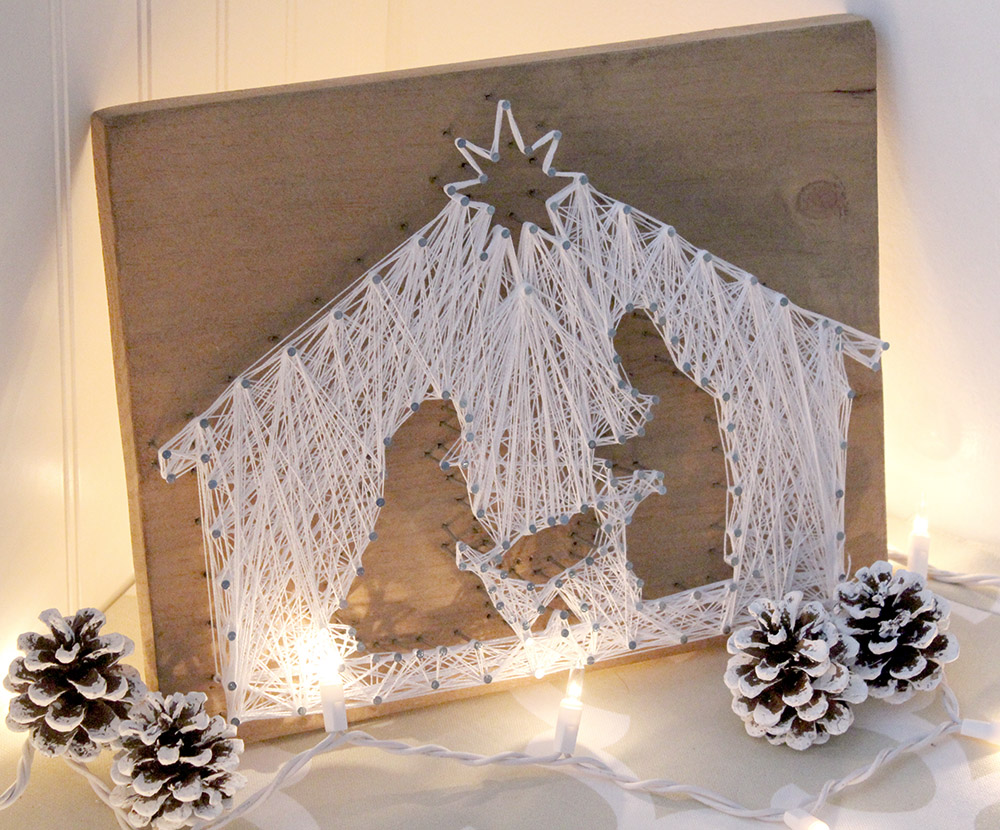 DIY nativity scene string art with pinecones and twinkle lights