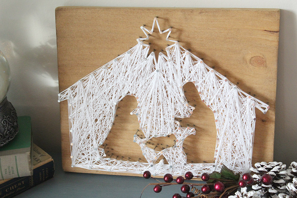 White string art nativity scene on wooden board