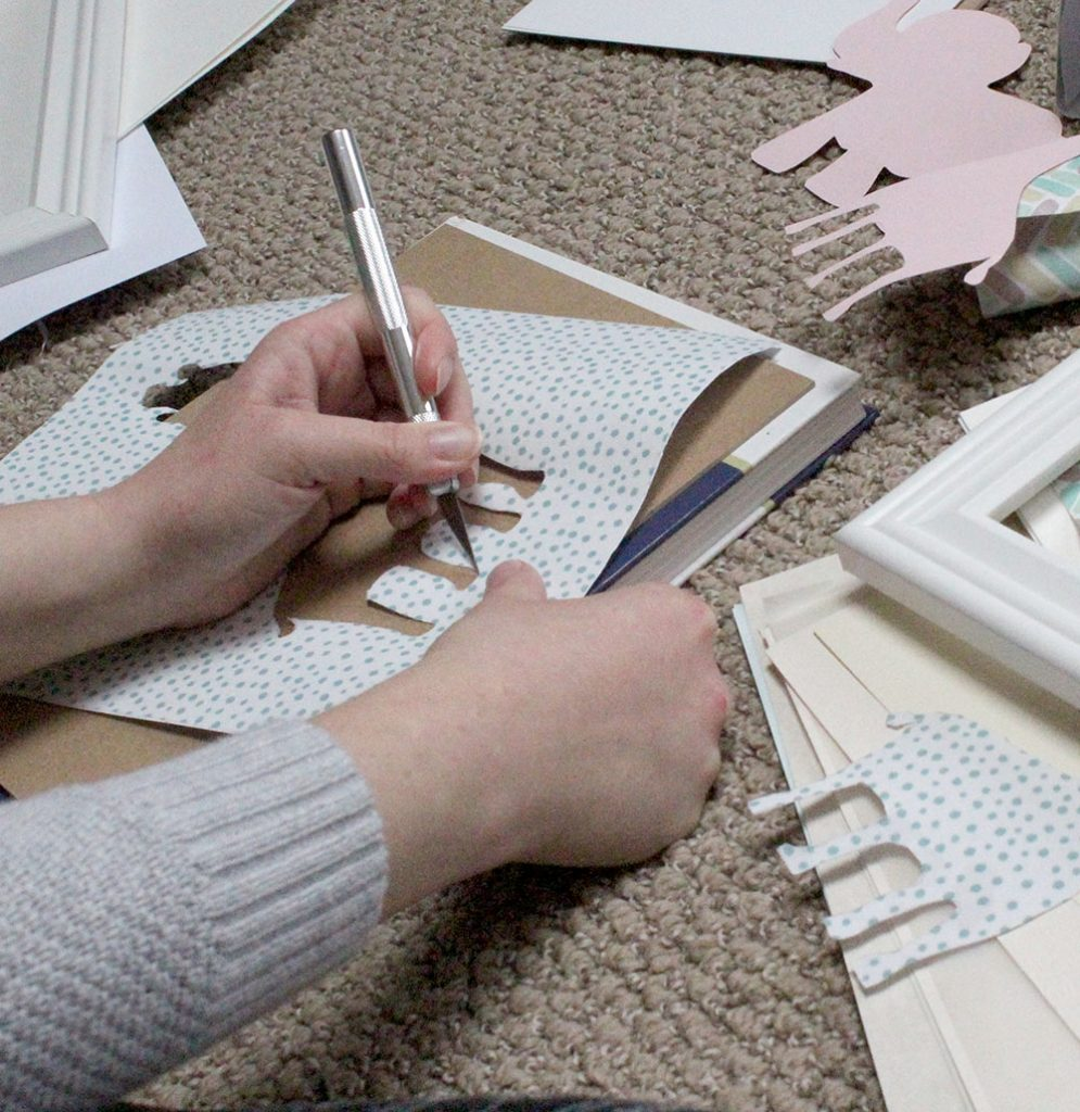 Using an X-acto knife to cut out animal nursery wall art