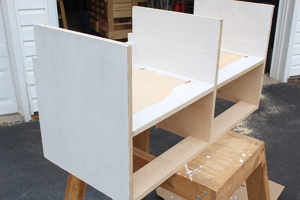 Using milk paint to the lower cubbies for the DIY entryway bench