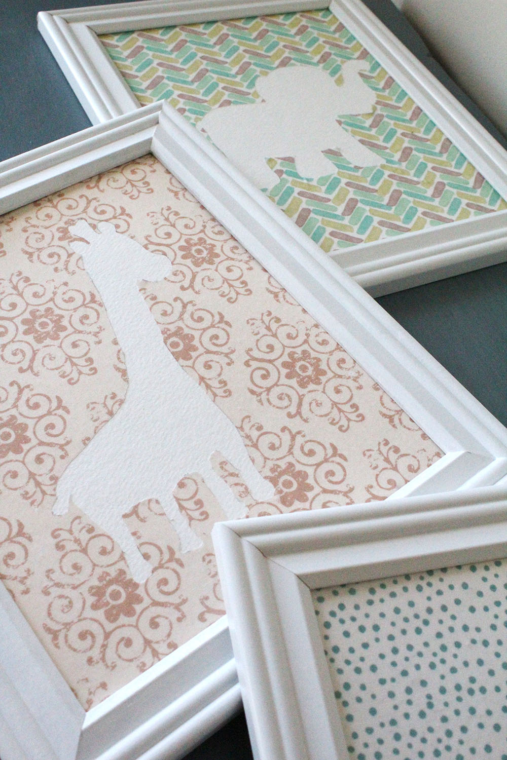 DIY nursery wall art with white picture frames, textured fabric paper, and baby animals