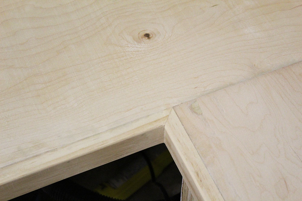 Sanding the edges of the benchtop trim of the DIY entryway bench with shoe storage