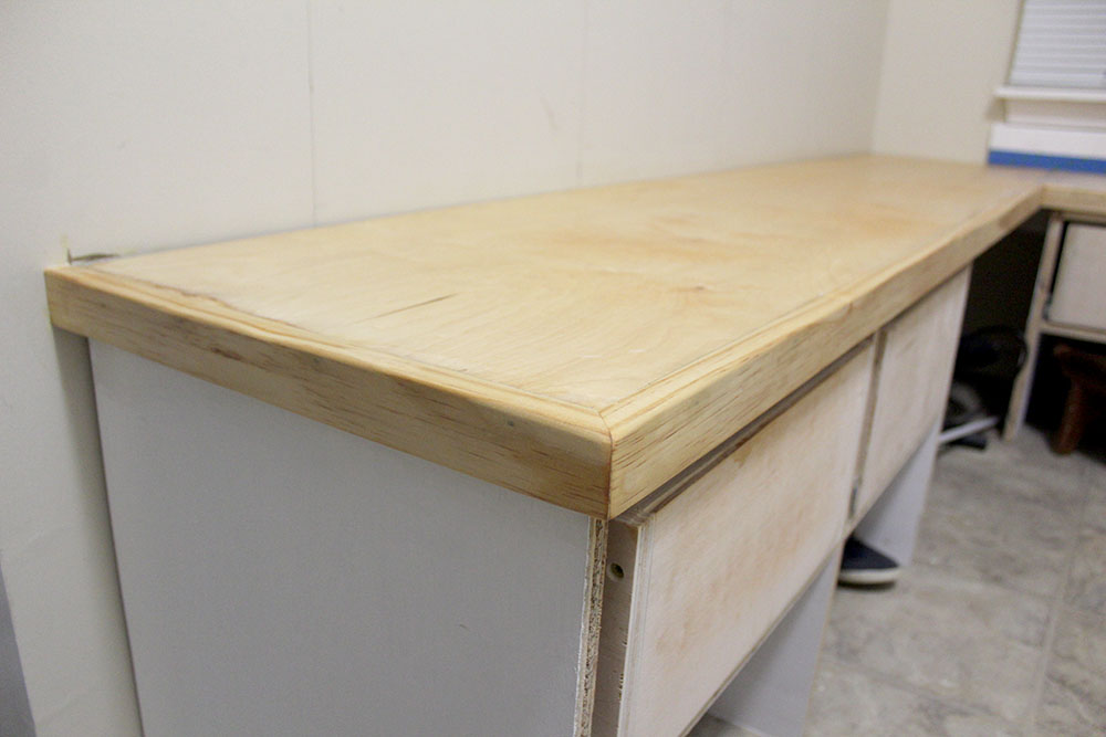 Covering the exposed benchtop plywood with custom-made trim for the DIY entryway bench