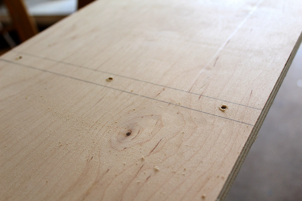 Predrilling pieces of wood for the upper cubby shelves on the entryway bench