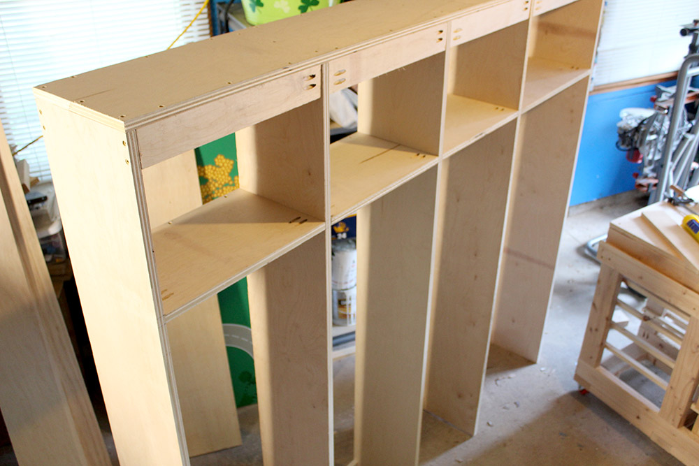 Finishing assembling the entryway hall tree with cubbies on this diy mudroom project