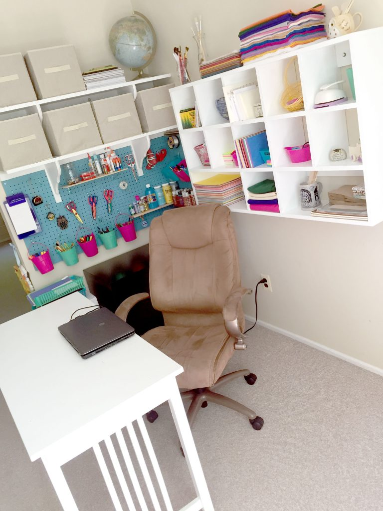 Organized craft room with pegboard, cubbies, and wall shelves