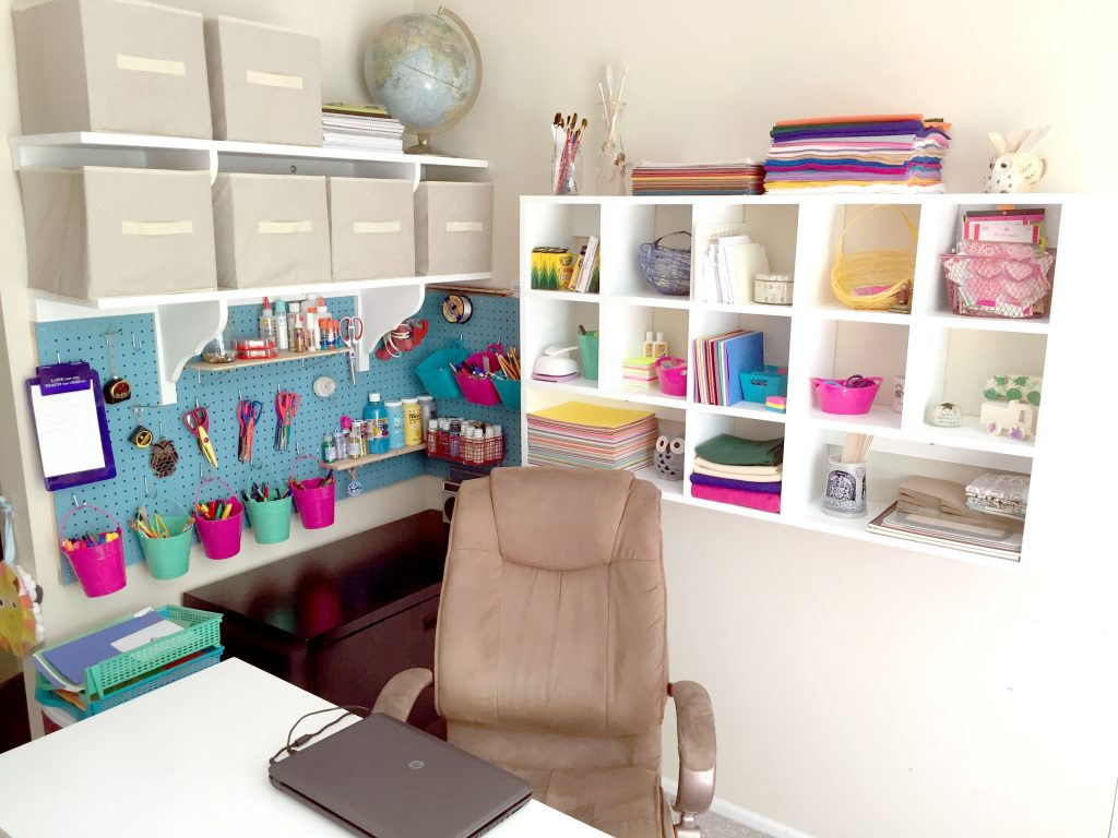 DIY craft corner with blue pegboard, wall-mounted cubby shelves, and fabric bin storage