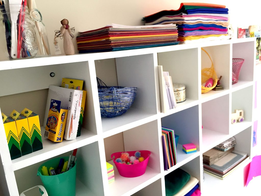 DIY cubby shelves mounted to the wall and organized with craft supplies