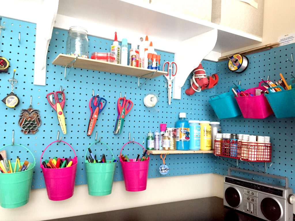 Blue wall-mounted pegboard and dollar store buckets for craft room organization