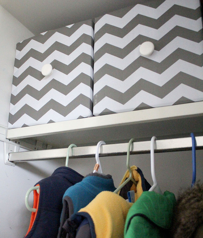 Gray and white chevron DIY storage cubes made from cardboard boxes on the top shelf of a coat closet