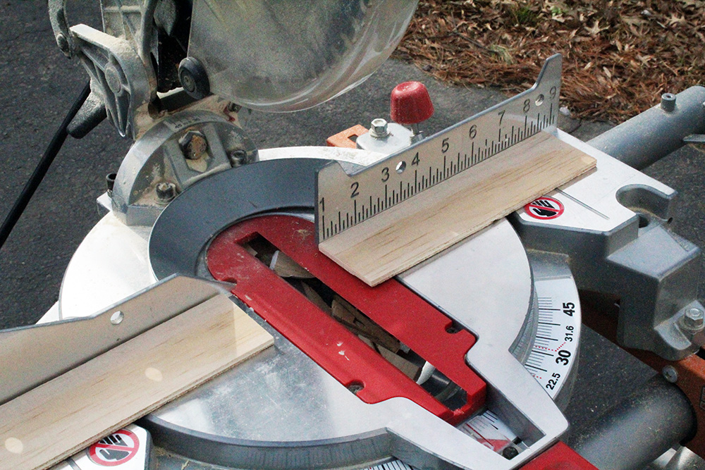 Using the miter saw to cut strips for the DIY swinging shelves