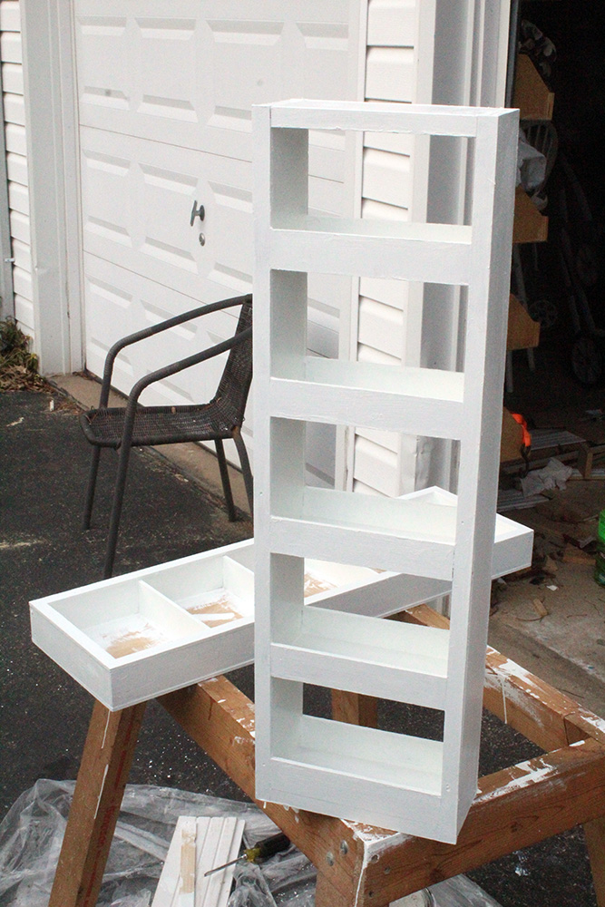 Painting a DIY wall shelf with a swinging shelf white for storing acrylic paints