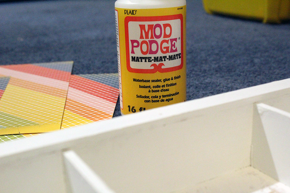Using mod podge and card stock on wood to create a colorful background for a DIY shelf