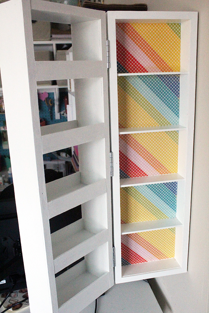 White DIY wall mounted cabinet with swinging shelf and colorful background