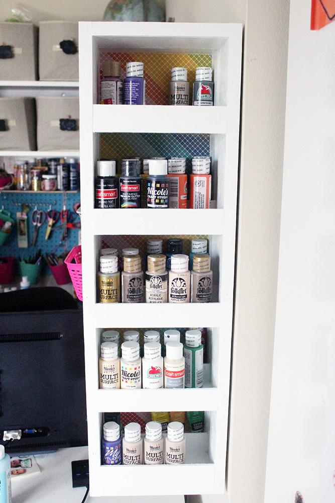 Swinging DIY shelf with hidden storage used for acrylic paint storage