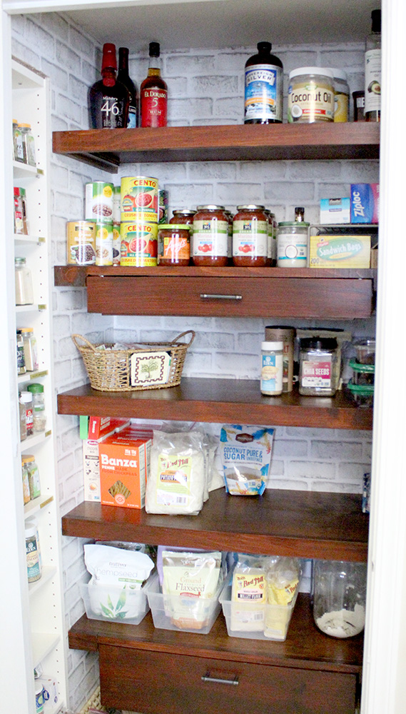 Kitchen pantry closet with wooden shelves and drawers and white brick wallpaper