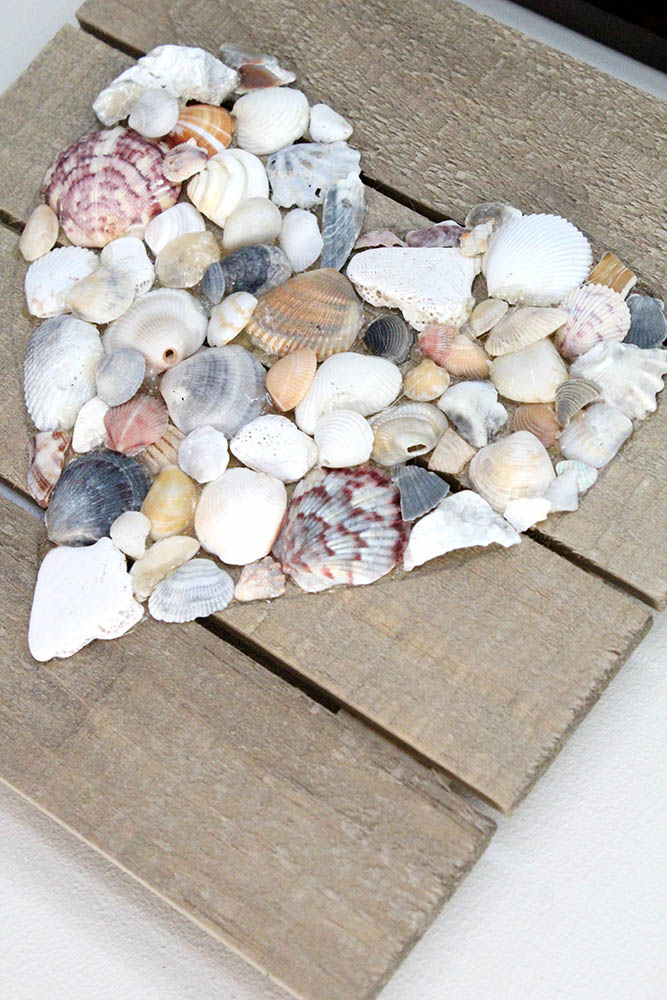 Heart shaped wall art made from seashells glued onto drift wood